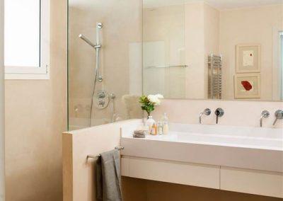 Baño en crema con ducha de obra separado del tocador con un cristal transparente a modo de mampara